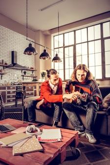 Onderwijs vriend. jonge getalenteerde geïnspireerde man met een rood vest die zijn vriend gitaar leert spelen