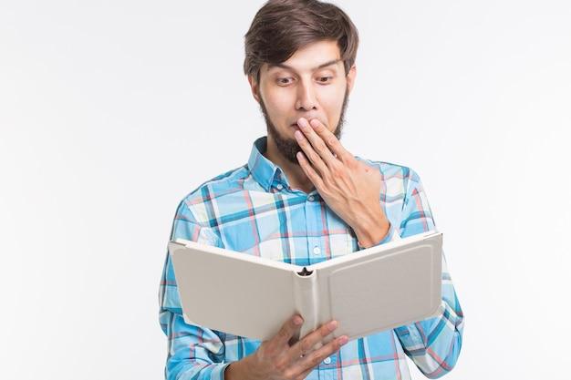 Onderwijs, vrije tijd en mensen concept - jonge baard man leest een boek en verrast.