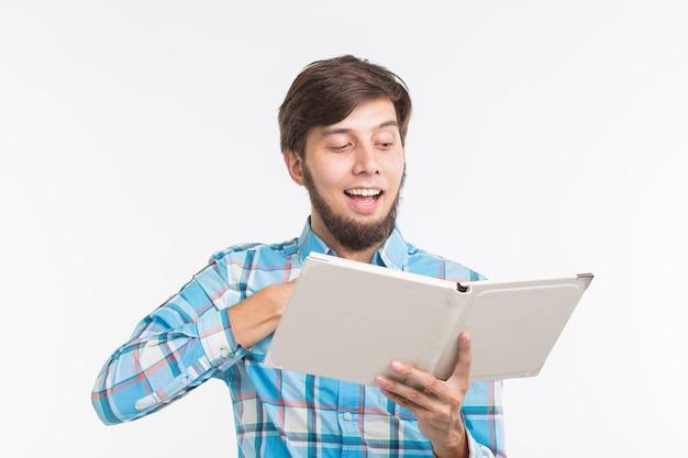 Onderwijs, vrije tijd en mensenconcept - jonge baardmens die een boek lezen en glimlachen Premium Foto