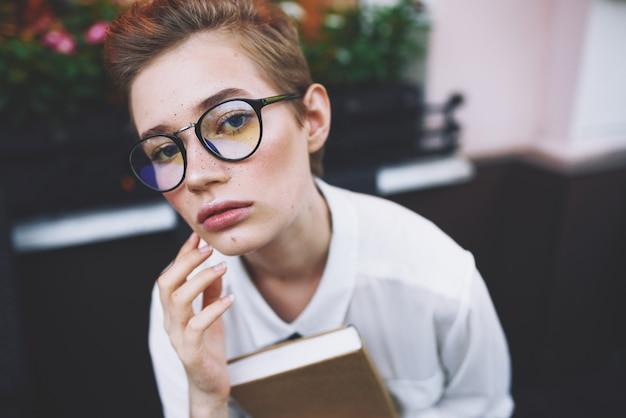 Onderwijs vrouw in glazen met boek aan tafel