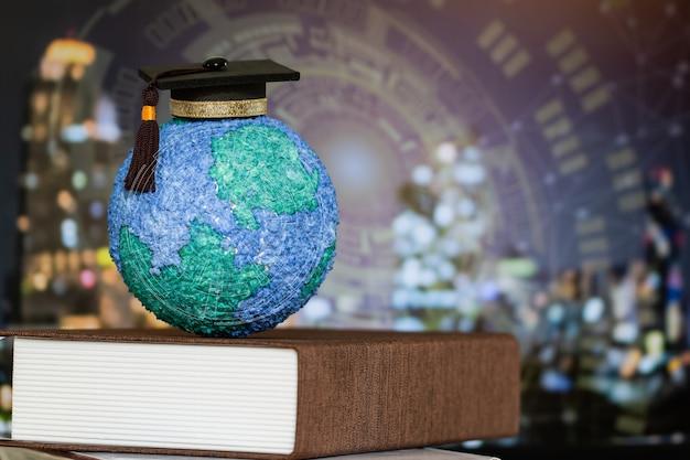 Onderwijs wereld kennis ideeën. graduation cap op modellen papier ambachtelijke earth globe op leerboek, vervagen hud grafische stad netwerk achtergrond. concept van succes bedrijfsstudie in het buitenland educatief