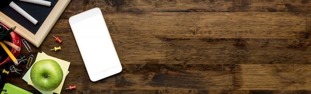 Onderwijsbenodigdheden met lege scherm mobiele telefoon op houten tafel achtergrond