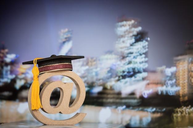 Onderwijscommunicatie in het buitenland internationaal concept: afstudeerpet op houten e-mailadressymbool op de achtergrond van de wazige stad. idee-succes voor contact op de universiteit van leren kan overal leren