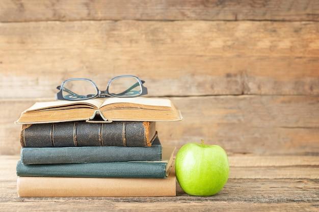 Onderwijsconcept boeken groene appel en glazen op het open boek op een houten achtergrond