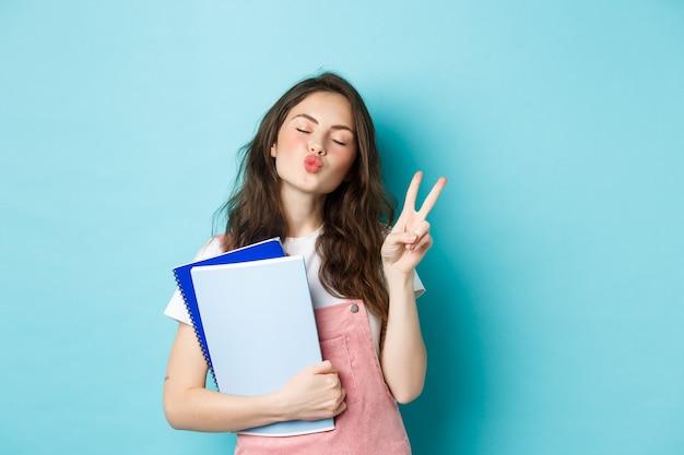 Onderwijsconcept. glimlachend glamourmeisje tuit lippen voor kus, toont v-teken vrede en houdt notitieboekjes vast voor studie, staande tegen een blauwe achtergrond