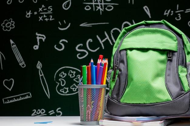 Onderwijsconcept - groene rugzak, notitieboekjes en schoolbenodigdheden op de achtergrond van het bord