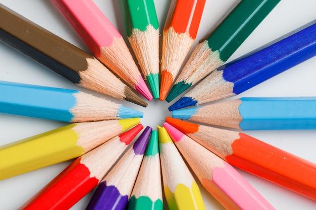 Onderwijsconcept met kleurpotloden op wit.