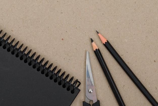 Onderwijsconcept met potloden, schaar, notitieboekje op papier.