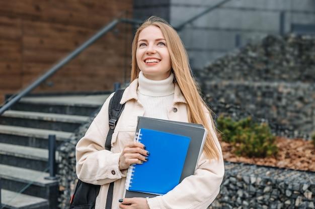 Onderwijsconcept. student meisje houdt mappen notebooks boeken in handen glimlacht, kijkt op tegen een universiteit