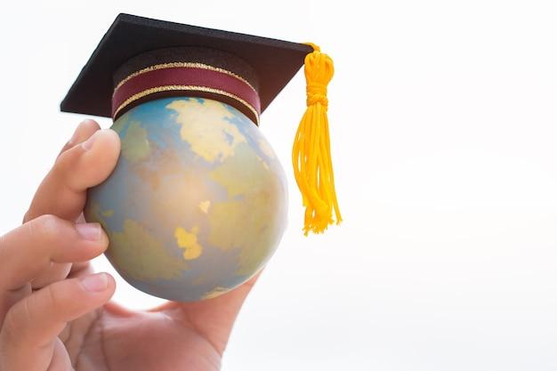 Onderwijswereld of afgestudeerde studie in het buitenland internationale ideeën. afstuderen hoed bovenop earth globe model kaart achtergrond. felicitaties aan afgestudeerden leiden tot succes in de wereld. terug naar school