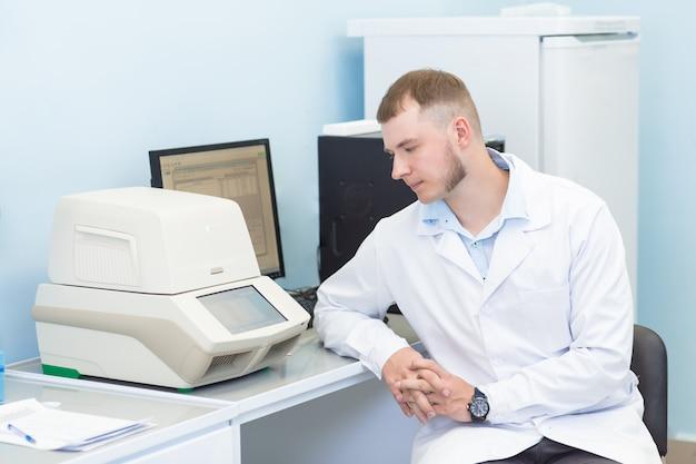Onderzoek of genetica wetenschapper met behulp van laptop in medische kantoor