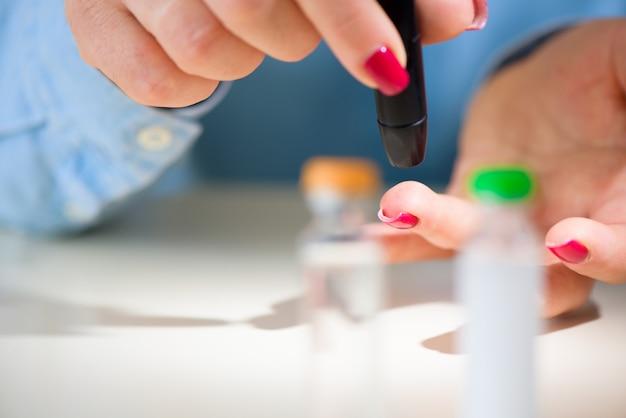 Onderzoek suiker. blokkeren van suikertesten, vingerprikken van vrouwenvingers. detailopname.