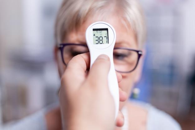 Onderzoek van lichaamstemperatuur van senior vrouw in ziekenhuiskamer tijdens onderzoekstest