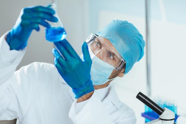 Onderzoeker die een vloeistof in een medische kolf bekijkt.