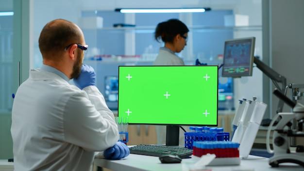 Onderzoeker die naar chroma key-display kijkt in een modern uitgerust laboratorium dat de virusevolutie analyseert. team van microbiologen die vaccinonderzoek doen en schrijven op apparaat met groen scherm, geïsoleerd, mockup-display.