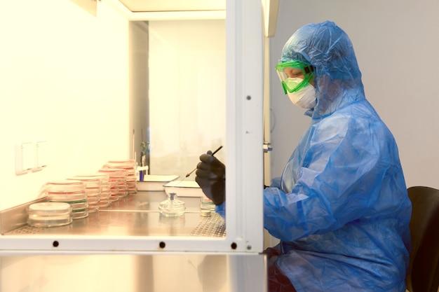 Onderzoeker die werkt met petrischaal met bacteriën in bacteriologisch laboratoriumconcept van