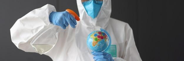 Onderzoeker in beschermend pak houdt ontsmettingsmiddel en wereldbol vast. coronovirus-pandemie in het wereldconcept