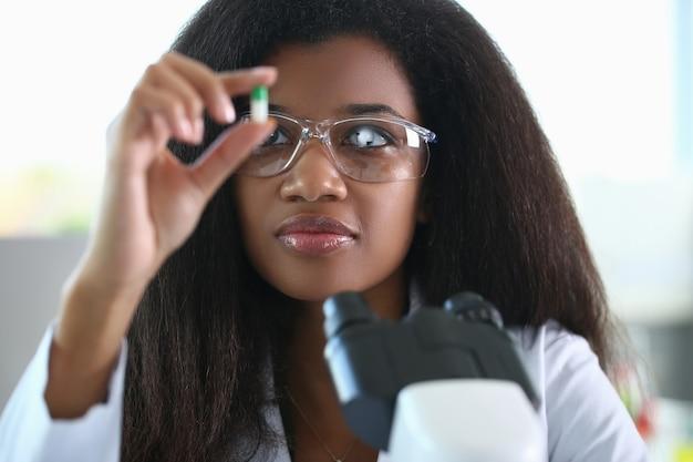 Onderzoeker met bril houdt capsule in zijn handen en kijkt ernaar