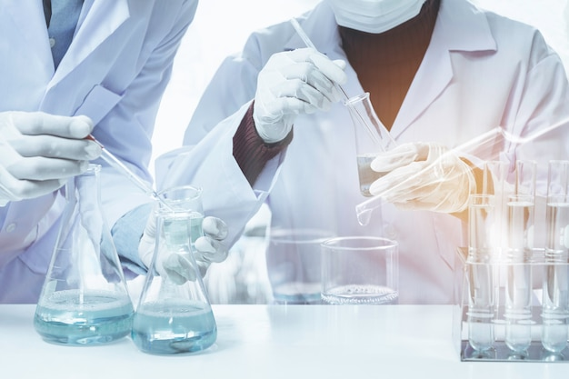 Onderzoeker met chemische testbuizen van laboratoriumglas met vloeistof voor analyse