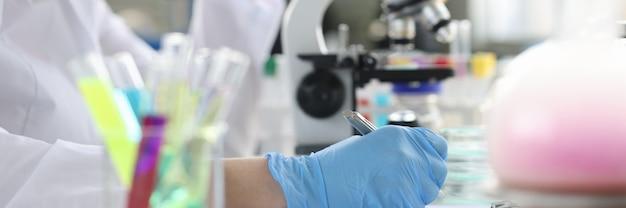 Onderzoeker met een bril werkt bij de microscoop en doet forensisch en medisch onderzoek