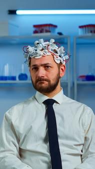 Onderzoeker neuroloog arts die de symptomen van de mens vraagt en aantekeningen maakt op het klembord voordat de hersenscan wordt uitgevoerd met een headset voor het scannen van hersengolven