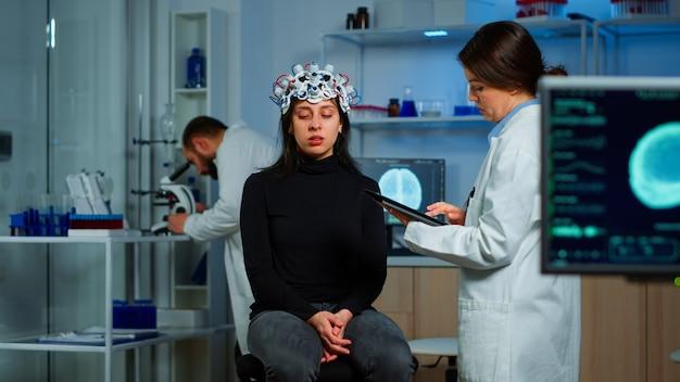 Onderzoeker neuroloog arts die de symptomen van de patiënt vraagt, notities maakt op tablet, high-tech eeg-headset aanpast. arts-onderzoeker die eeg-headset bestuurt en hersenfuncties en gezondheidsstatus analyseert