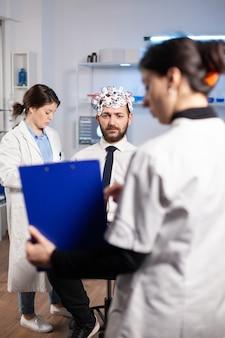 Onderzoeker neuroloog arts die de ziektesymptomen van de mens vraagt en naar het klembord kijkt voordat de hersenscan wordt uitgevoerd met een headset voor het scannen van hersengolven. wetenschapper die gezondheidsstatus, zenuwstelsel, tomografiescan analyseert.