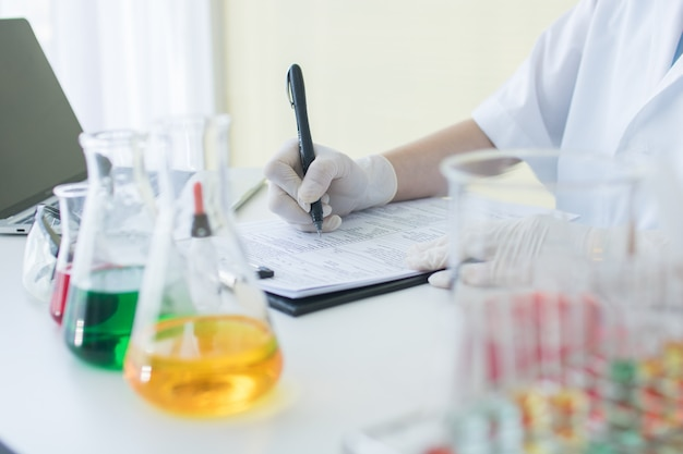 Onderzoeker of wetenschapper die informatieresultaat en nota op papier in wetenschapslaboratorium schrijft