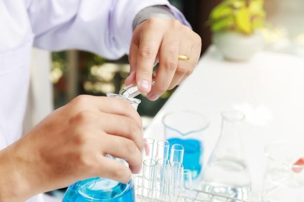 Onderzoeker of wetenschappers laden vloeibaar monster in het bekerglas in het laboratorium.