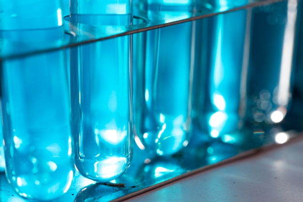 Onderzoekers gebruiken glaswerk en blauwe oplossingen in laboratoria, onderzoek naar cosmetica en energie.
