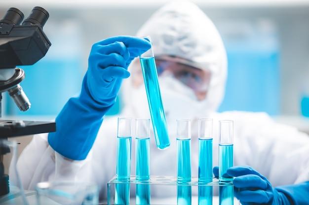 Onderzoekers wetenschapper werkende analyse met blauwe vloeistof reageerbuis in het laboratorium, scheikunde of medische biologie experimenttechnologie, apotheek ontwikkelingsoplossing