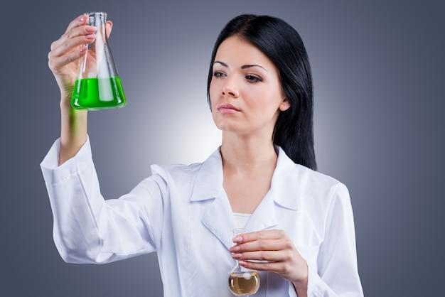 Onderzoeksstudies. mooie vrouwelijke arts in wit uniform die kolven vasthoudt terwijl ze tegen een grijze achtergrond staat