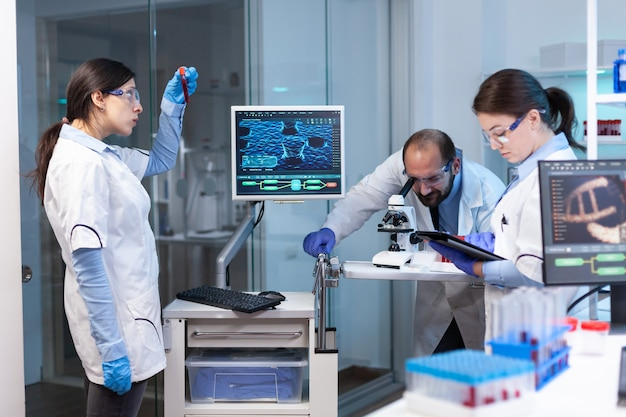 Onderzoekswetenschappers die werken aan een monitor met medische apparatuur die bloed analyseert, monsters van genetisch materiaal