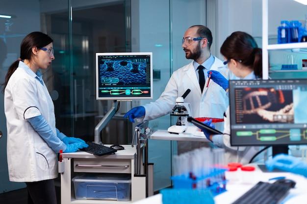 Onderzoekswetenschappers werken aan monitor die virus analyseert met chemieteam