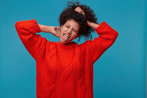 Ondeugend eigenzinnig latino meisje met donker krullend haar verzamelt het in een ponitail, boog haar hoofd en toont haar tong, gekleed in een rode oversized trui