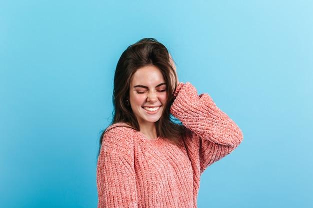 Ondeugend meisje maakt schattige gezichtsuitdrukking op blauwe muur. donkerharige vrouw in warme trui lacht.