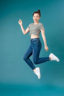 Ondeugend meisje met gestreept t-shirt en spijkerbroek aan het dansen