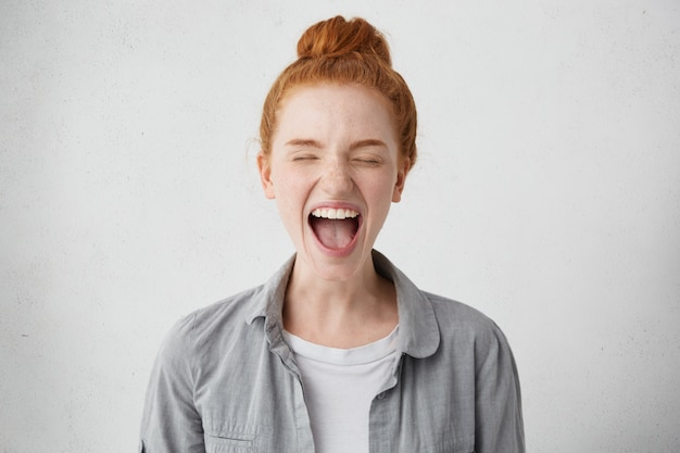 Ondeugend verwend tienermeisje met rood haar werd hysterisch, sloot de ogen stijf en opende haar mond in een gil om protest, ongehoorzaamheid uit te drukken