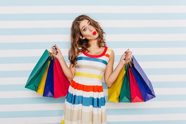 Ondeugend, vrolijk meisje maakt een schattig en grappig gezicht, poseren met kleurrijke papieren pakketten. sluit portret van bruinharige vrouw met rode lippenstift, gelukkig na succesvol winkelen