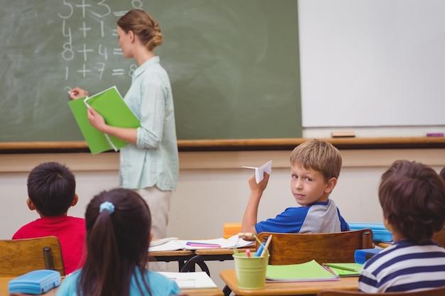 Ondeugende leerling op het punt om papieren vliegtuigje in de klas te gooien
