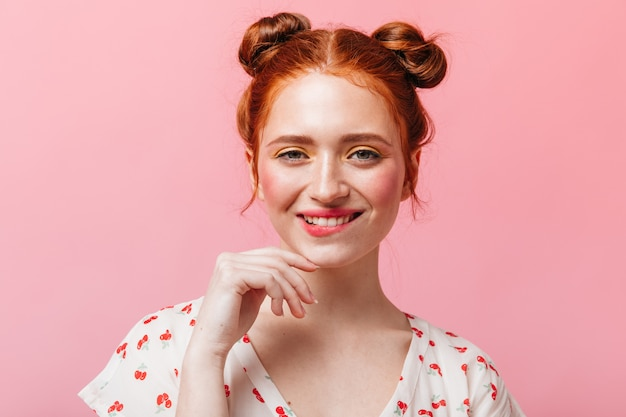 Ondeugende roodharige dame met lichte make-up knipoogt en glimlacht op roze achtergrond.