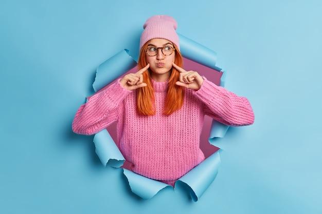 Ondeugende roodharige vrouw houdt lucht in wangen en wijst met wijsvingers maakt grappige grimas draagt hoed en gebreide wintertrui.