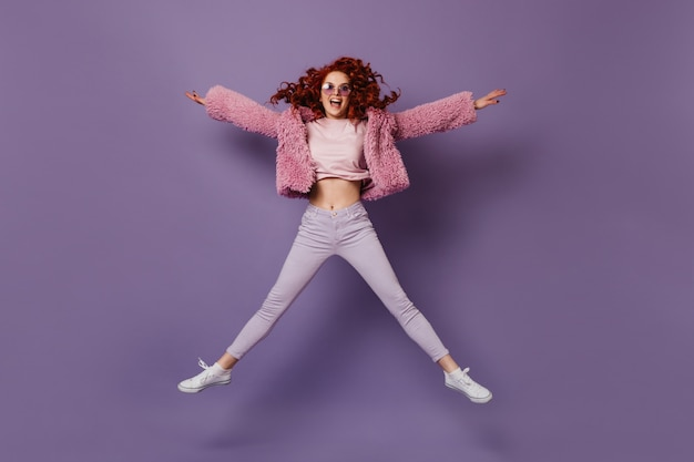 Ondeugende vrouw in lila bril, witte broek, t-shirt en roze eco-jas die op lila ruimte springt.