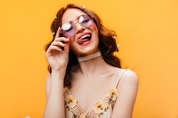 Ondeugende vrouw in lila zonnebril likt haar lippen en poseren op een oranje achtergrond.