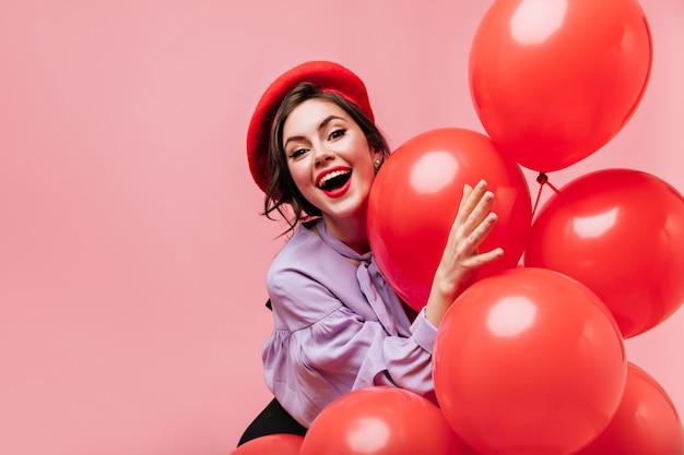 Ondeugende vrouw in rode baret lacht en heeft plezier op roze achtergrond met grote ballonnen.