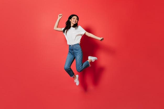 Ondeugende vrouw in wit t-shirt en spijkerbroek springen op rode muur