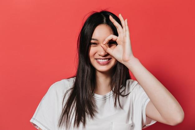 Ondeugende vrouw in witte top lacht en toont ok teken