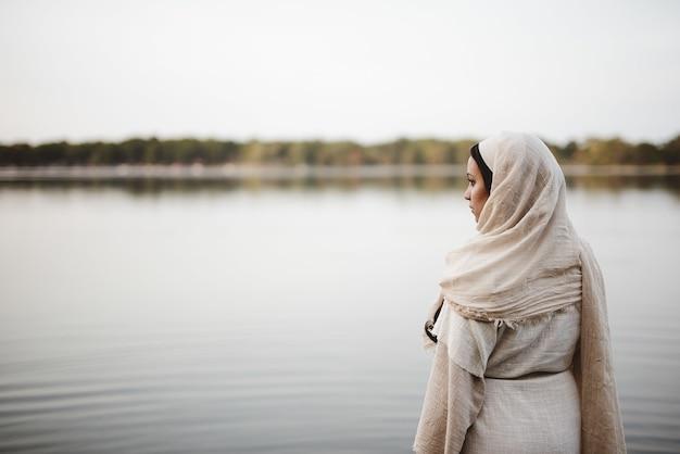 Ondiepe focus geschoten van achteren van een vrouw die een bijbelse jurk draagt terwijl ze in de verte kijkt