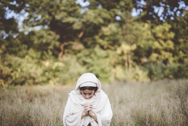 Ondiepe focus shot oa een vrouw die bidt terwijl ze een bijbels gewaad draagt