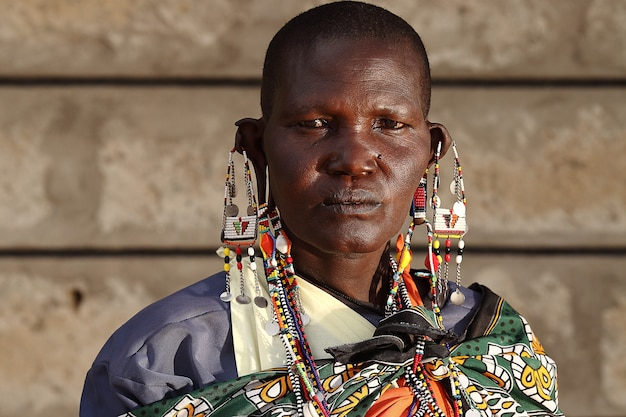 Ondiepe focus shot van een afrikaanse man met grote oorbellen tijdens het kijken naar de camera